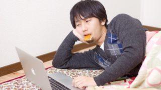 横になってmacbookを操作する男性