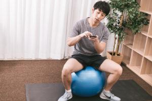 運動しながらスマホを操作する男性