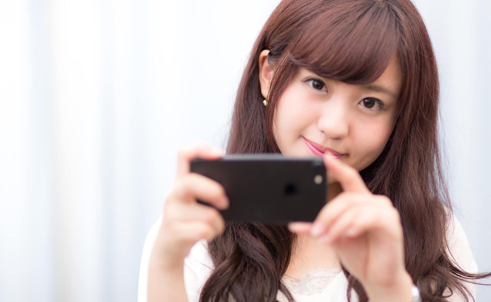 iPhoneでPS4のリモートプレイを使う女性