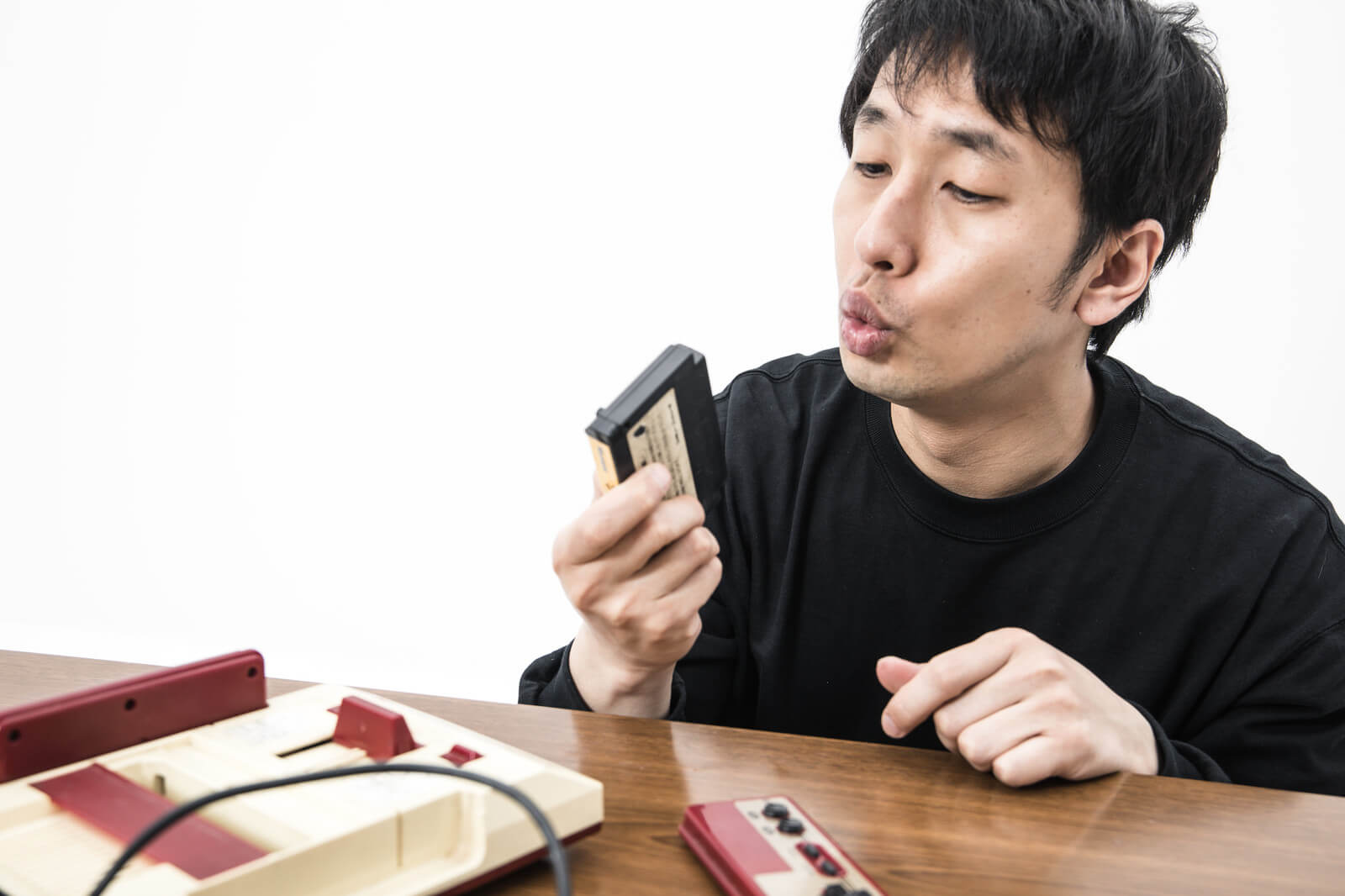ファミコンのカセットをフーフーする男性